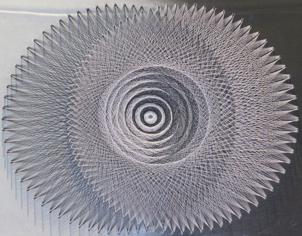 """Fine Thread art by Rob Monroe. Title """"Layer 13"""" Thirteen layers of interlaced black and white thread in two overlapping circles, each focusing at the same point."""